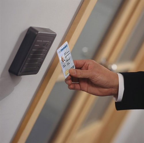 image of a man swiping a key card over the access control pad in an office building